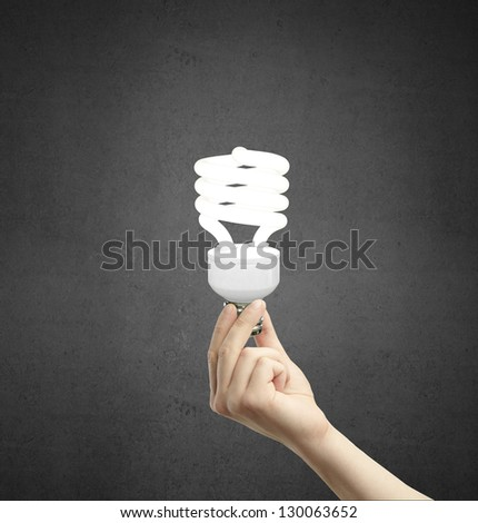 hand holding energy saving lamp on a concrete background - stock photo