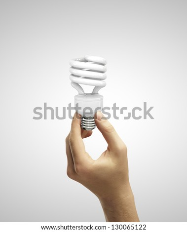 hand holding energy saving lamp  on a white background - stock photo