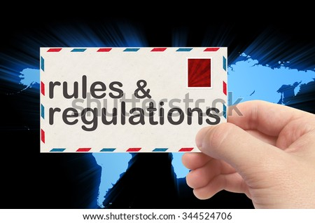 hand holding envelope with rules and regulations word and world background. - stock photo