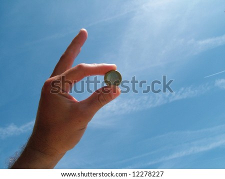 Hand holding Euro coin - stock photo