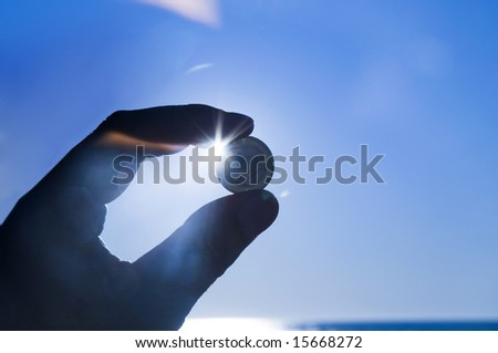 Hand holding Euro coin against blue sky - stock photo