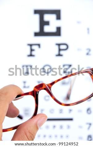 hand holding eye glasses ,optometry concept - stock photo