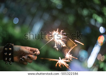 Hand holding firecracker that spark spreading out