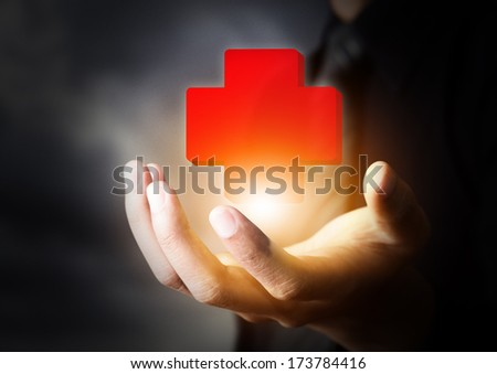 Hand holding First Aid icon, insurance concept - stock photo