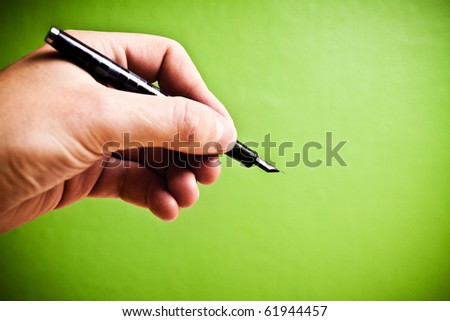 Hand holding fountain pen on green background - stock photo
