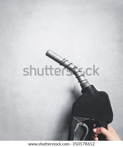 hand holding fuel nozzle pump with gray background - stock photo