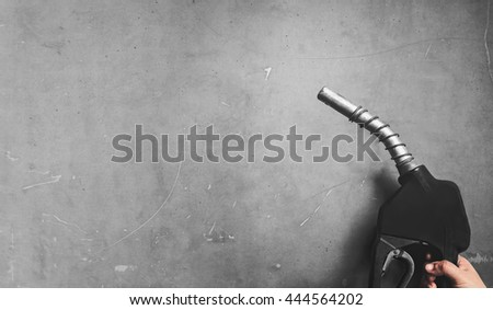 hand holding fuel nozzle pump with gray textured background