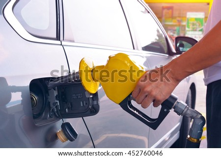 Hand holding fuel nozzle to add gas at petrol station.