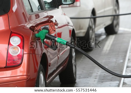 Hand holding fuel nozzle to add gas. Car refueling on a petrol station. Fuel, energy, ecology concept.