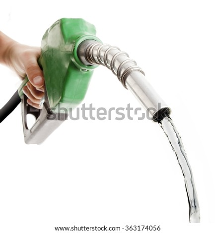 Hand holding fuel nozzle wasting gas on white - stock photo