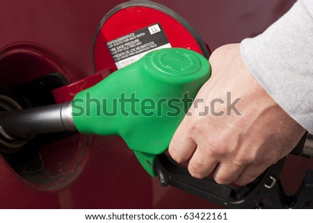 Hand Holding Fuel Pump Refilling Car - stock photo