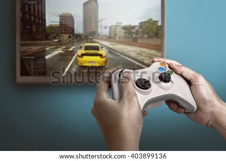 Hand holding game console controller playing racing game on the television - stock photo