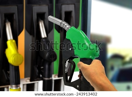 Hand holding Gas Nozzle at Gas Station - stock photo