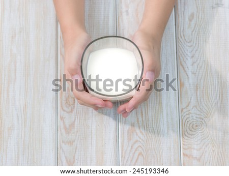 hand holding glass of milk on wood table  - stock photo