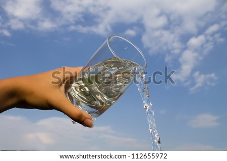 Hand holding glass with water pouring down - stock photo