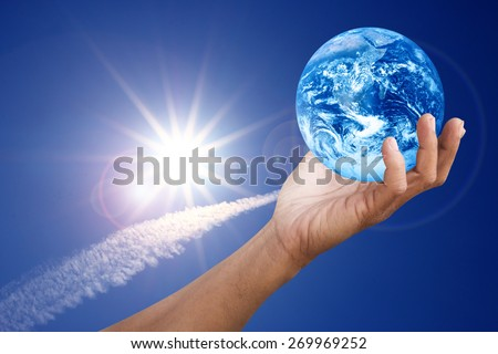 Hand holding global over contrail cloud with blue sky and fairy sparkle sun with flare ?Elements of this image furnished by NASA - stock photo