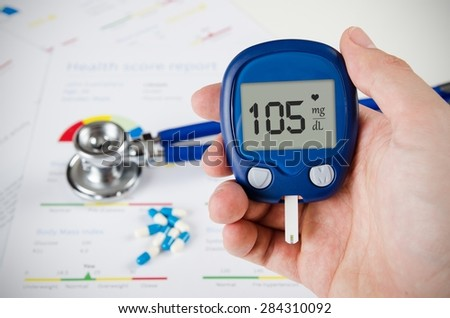 Hand holding glucometer. Stethoscope and pills in background - stock photo