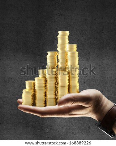 hand holding gold coins city - stock photo