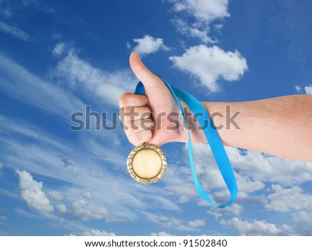 Hand holding gold medal on sky background - stock photo