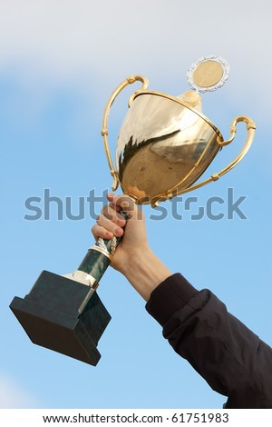 hand holding golden trophy - stock photo