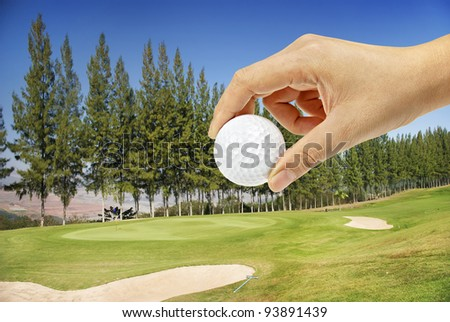 Hand holding golfball in golf course on hill