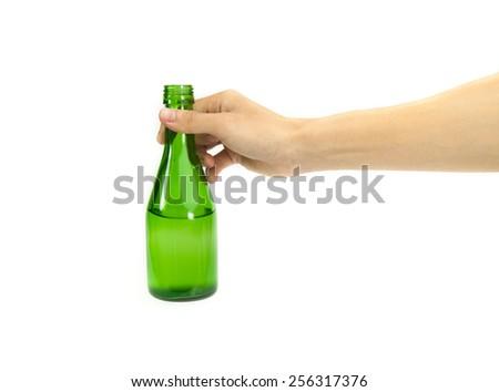 hand holding green bottle isolated on white background. - stock photo