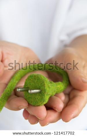 hand holding green electric plug - stock photo