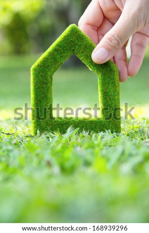 Hand holding green house icon with nature background