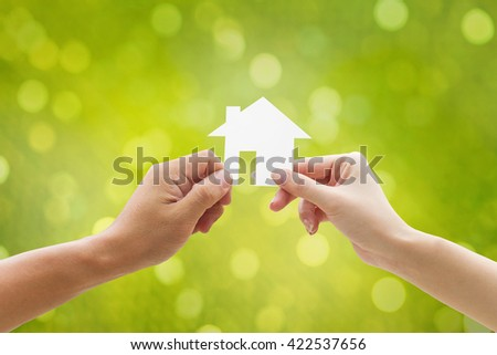 Hand holding house on green background