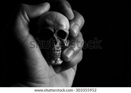 hand holding human skull on low key photograph