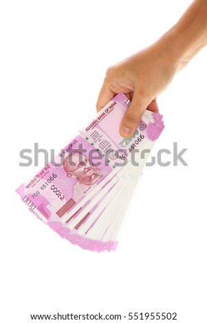 Hand holding Indian 2000 rupee notes against white background