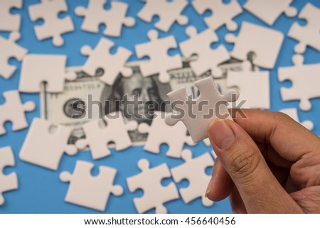 hand holding jigsaw, banknote money on background