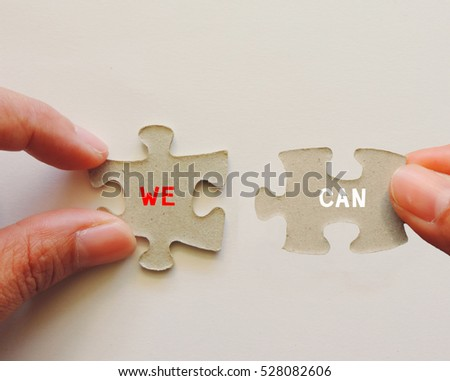 "Hand holding jigsaw puzzle with word""WE CAN"""
