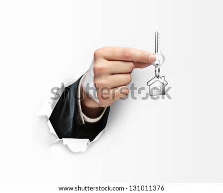 hand holding key and torn paper - stock photo