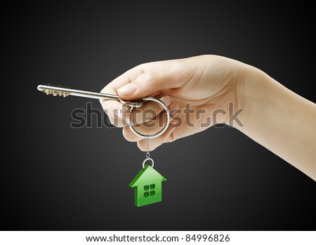 Hand holding key with a keychain in the shape of the house. House key on a black background - stock photo