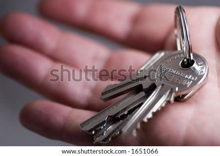 Hand holding keys (very shallow DOF) - stock photo