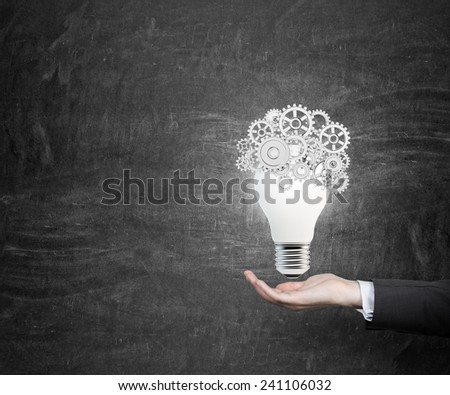 hand holding lamp with cogs and gears - stock photo