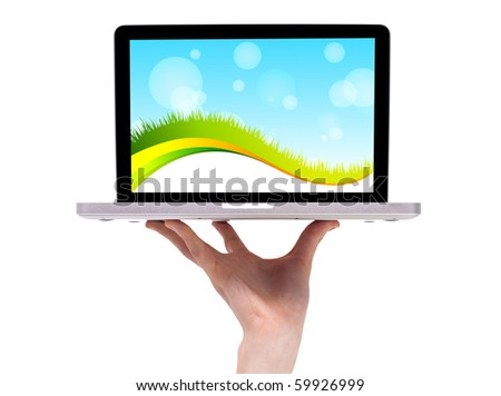 Hand holding laptop with abstract green wallpaper - stock photo