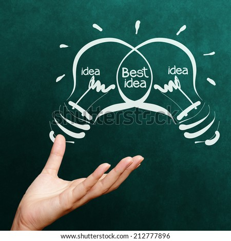 hand holding Light bulb  best idea on blackboard background as concept - stock photo