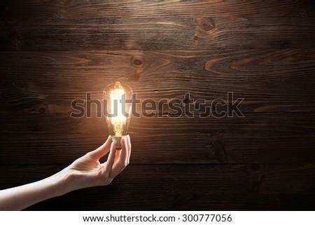hand holding Light bulb on blackboard background - stock photo