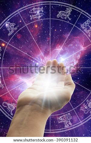hand holding light in front of a zodiac chart - stock photo
