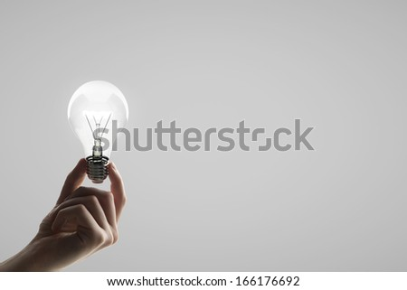 hand holding lightbulb on a gray background - stock photo