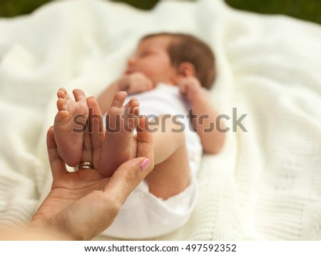 Hand holding little baby's legs