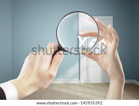 hand holding magnifying glass and  yen, dollar and euro - stock photo