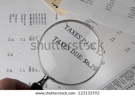 Hand holding magnifying glass showing the words taxes paid and due on financial paper