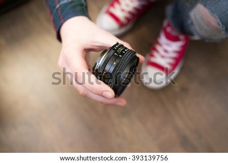 Hand holding manual prime lens 50 mm on dark background - stock photo