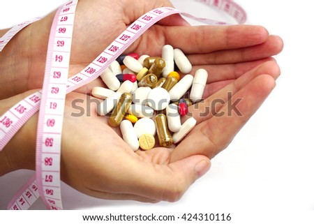 hand holding medicines, pills and measuring tape isolated on a white background.  Dieting concept, healthcare and medical background  - stock photo
