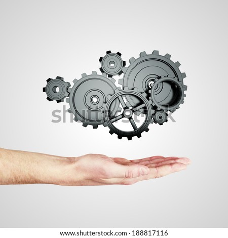 hand holding metal gears and cogwheels on gray background - stock photo