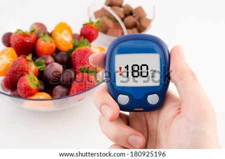 Hand holding meter with warning glucose level test. Fruit and chcolates in background. - stock photo