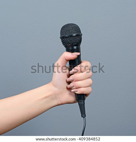 Hand holding microphone against gray background - stock photo